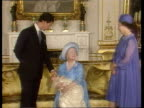 CHRISTENING ENGLAND CMS Queen Mother holding crying baby PULL OUT London Prince Charles and Queen look on Buckingham CMS Ditto PULL OUT Queen and...