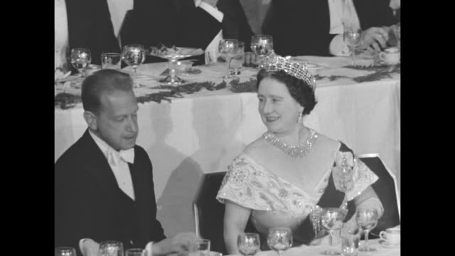 MS Queen Mother seated at table next to Columbia University President Dr Grayson Kirk / WS as all are standing Queen Mother is seated / MS Queen...