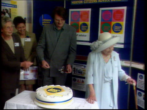 Queen Mother's 99th birthday LIB INT Queen Mother cutting cake as comedian Paul Merton looks on
