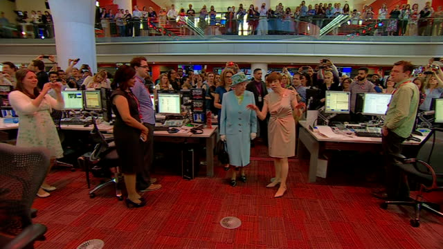 Queen officially opens BBC's New Broadcasting House Newsroom staff standing beside desks / Queen along with Mary Hockaday and Unsworth showing her...