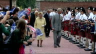Queen visit to Dumfries House EXT Royal group into walled garden / Queen and Charles walking through pipers and schoolchildren / Queen shaking hands...