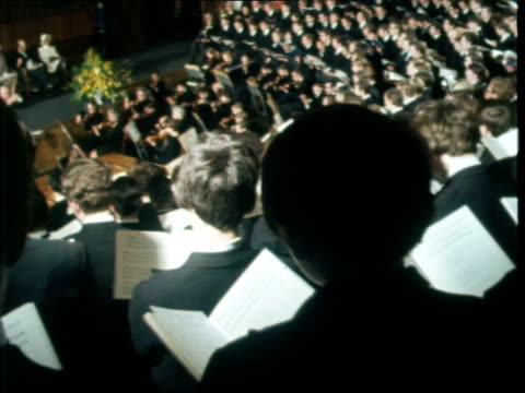 Queen visit to Harrow School School assembly singing school song SOF Queen sat listening Conductor and orchestra with assembly