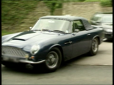 Gloucestershire EXT Sports car driven by Prince of Wales out of Highgrove House grounds PAN and away