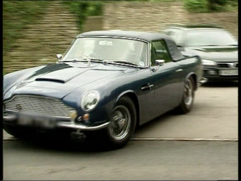 Gloucestershire Sports car driven by Prince of Wales out of Highgrove House grounds PAN and away ENGLAND London GV Newspaper stall