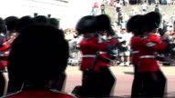 London EXT Guards band marching wearing bearskin hats Protestor demonstrating against use of bearskins dressed as bear watching parade Military band...