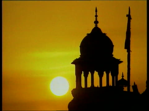 Queen's visit Dilomatic row NAT Amritsar Sunset Sunset rising over temple as prayers are called SOT Sikh man standing praying as others walk by CS...