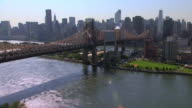 AERIAL Queensboro Bridge passing over Roosevelt Island and East River / New York City, New York, United States