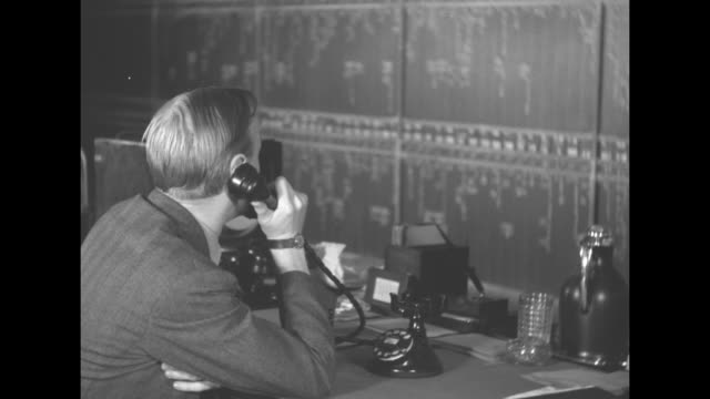 right profile of blond man CU rotary telephone dial with number 'WHitehall 4 9970' / VS workers with ticker tape at stock exchange tote board / the...