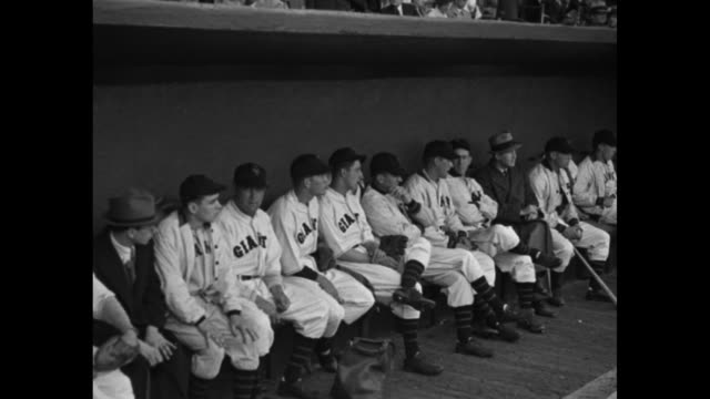 'NY Giants play Phils in Opener' / players walking across Polo Grounds baseball field in unison / VS buntingdecorated grandstands / press gathered at...