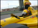 Race car driver in Indy car in pit putting on gloves / Nazareth, Pennsylvania