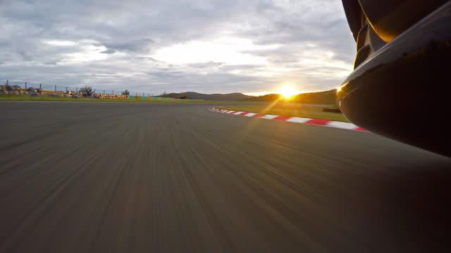 Race car driving towards the sunset