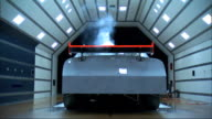 Race car viewed from rear in active wind tunnel white smoke streaming over hood of car toward camera NASCAR technology science scifi testing...