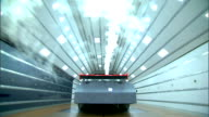 Race car viewed from rear in active wind tunnel with white lights on ceiling brown floor white smoke streaming over automobile toward camera NASCAR...