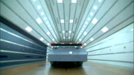 Race car viewed from rear in wind tunnel with white lights on ceiling brown floor NASCAR science Scifi testing laboratory aerodynamics