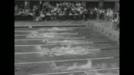 Race start at Empire Pool during Summer Olympics in London / man with garment over head in summer heat / swimmers approach end of pool / underwater...