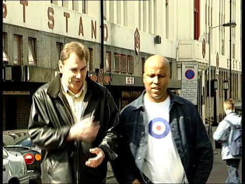 Background ITN ENGLAND London Highbury EXT Ewart walking along with Billy Grant Billy Grant interview SOT Twenty years ago you'd go onto the terraces...