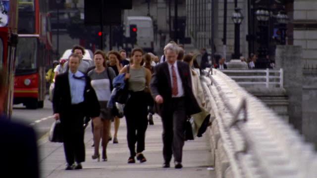 rack focus businesspeople walking on London Bridge / London, England