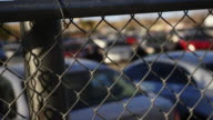 Rack focus, cars in impound lot behind fence