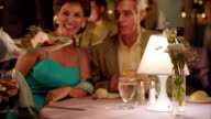 rack focus from close up dishes of food to MS waiter serving them to middle age couple in upscale restaurant