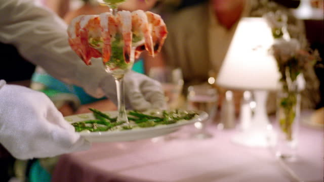 rack focus from close up shrimp cocktail to MS waiter serving it to middle age couple in upscale restaurant