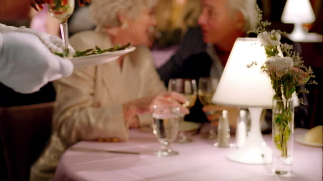 rack focus from close up shrimp cocktail to MS waiter serving it to senior couple in upscale restaurant