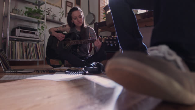 Rack focus from tapping foot to woman playing guitar in apartment jam session.