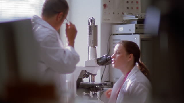 Rack focus medium shot man and woman in lab coats taking turns looking through microscope in office