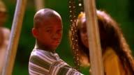 MS rack focus PORTRAIT Black boy + Black girl sitting on swings / Florida