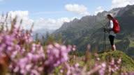 Rack focus view as female hiker walks through alpine meadow