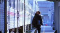 Rack focus wide shot businesswoman getting out of train / businessman hugging her / couple walking away