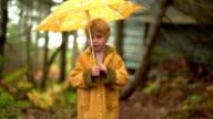 Rack focus young blonde girl in raincoat with umbrella walking through trees toward camera / Nova Scotia
