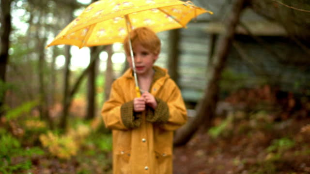 Rack focus young blonde girl in raincoat with umbrella walking through trees toward camera / Nova Scotia