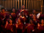 rack focus zoom out Black gospel choir in robes singing + clapping in church / finish + talk