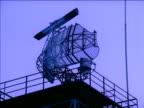 Radar scanner rotating on platform against sky at dusk