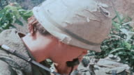 Radio operator talking on field telephone and 101st Airborne Division soldiers forming up patrol and moving out / Vietnam
