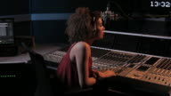 DJ radio presenter operating controls in studio