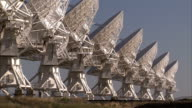 Radio telescopes form a line in the desert. Available in HD.