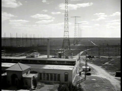 Radio towers to rural horizon line relay station below Radio towers wires Male technician working adjusting dials on tall control panel