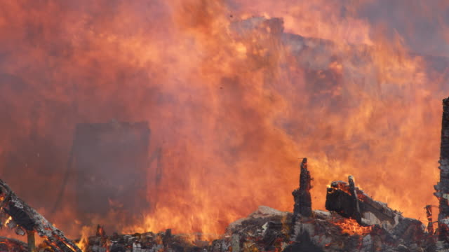 Raging flames consume the collapsing remains of a burning house, charred rubble in foreground