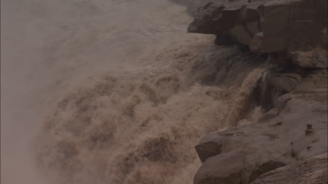 Raging torrent of water floods over falls, Hukou Falls.