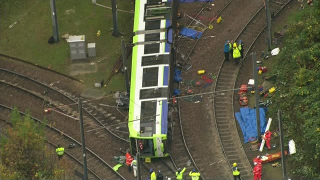 Croydon tram derailment trams begin running again LIB / T09111627 derailed and overturned tram with emergency service workers at scene