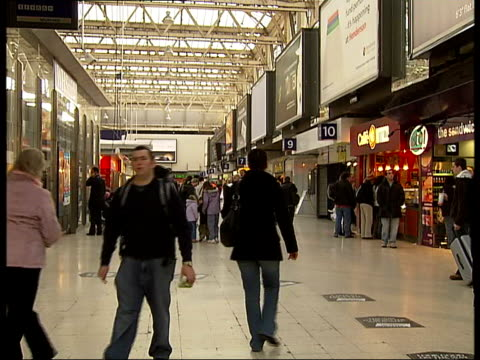 South West Trains begins new tenyear franchise Trains and passengers at station Destination boards PAN / passengers around on station concourse /...