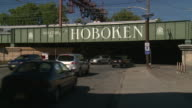 A railway bridge with a sign 'Welcome to Hoboken'  Cars drive underneath the bridge.  A train goes across the bridge.