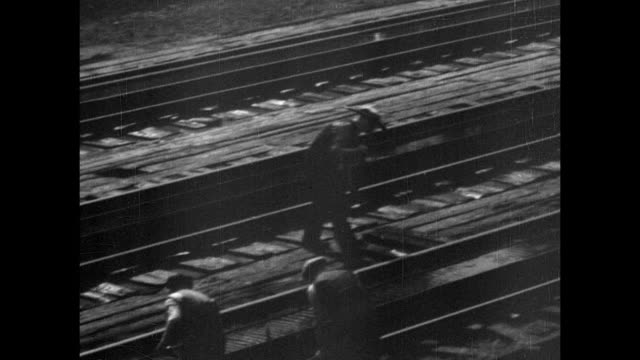 MONTAGE Railway laborers digging on a railroad track and standing clear when a train comes speeding through / United Kingdom