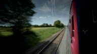 Railway line alongside red train carriage.