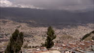 Rain clouds loom over a Bolivian valley city. Available in HD.