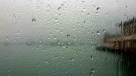 Regen druppels druipen beneden het glas van venster