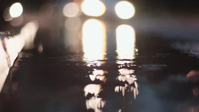 Rain drops splashing water surface in the street