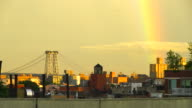 Rainbow appears over the East Village Manhattan New York at dusk. Williamsburg Bridge can be seen behind East Village cityscape.