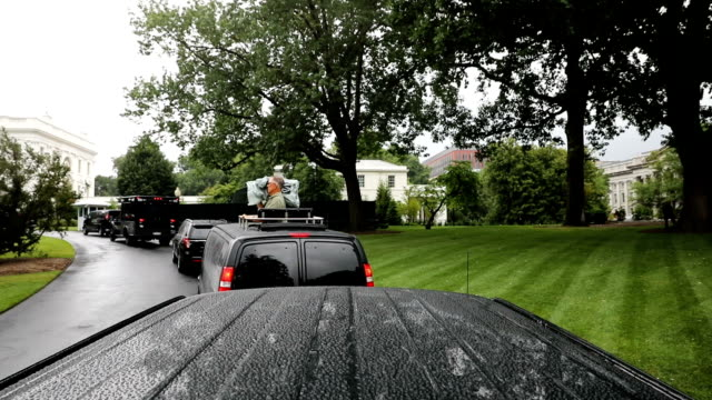 A rainy view from the press vehicle's rooftop as it travels along the White House south circle drive as part of President Donald Trump's motorcade to...